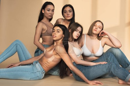 Photo for Five dreamy multicultural young women sitting in sunlight and looking at camera, body positivity concept - Royalty Free Image