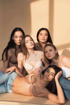 Foto de Cinco hermosas mujeres multiculturales mirando a cámara en luz del sol, del cuerpo concepto de positividad - Imagen libre de derechos