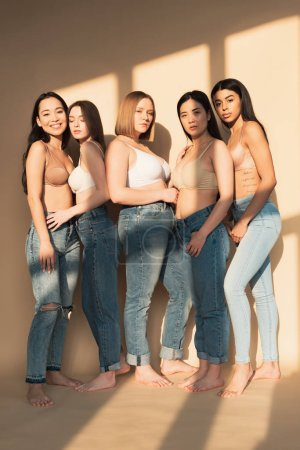 Photo pour Five beautiful multicultural women in blue jeans and bras standing together in sunlight, body positivity concept - image libre de droit