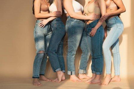 Foto de Vista parcial de cinco mujeres en jeans azul y bras de pie juntos en la luz del sol, concepto de positividad de cuerpo - Imagen libre de derechos
