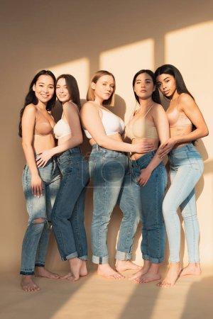 Foto de Cuerpo de cinco atractivas mujeres multiculturales en jeans azul y bras de pie en la luz del sol y mirando a cámara, concepto de positividad - Imagen libre de derechos
