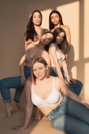 Foto de Enfoque selectivo de cinco chicas multiculturales posan a cámara en luz del sol, concepto de positividad de cuerpo - Imagen libre de derechos