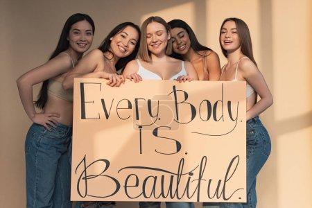 """Foto de Cinco niñas alegres multiculturales con pancarta con la inscripción """"cada cuerpo es perfecto"""" - Imagen libre de derechos"""