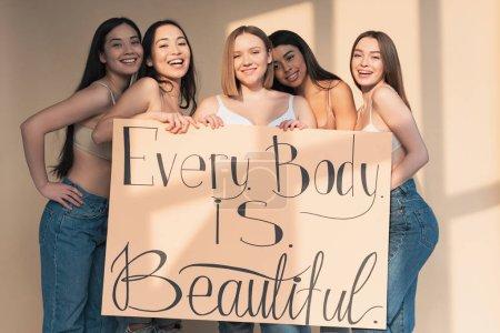 """Foto de Cinco niñas multiculturales felices sosteniendo pancarta con letras """"cada cuerpo es perfecto"""" - Imagen libre de derechos"""