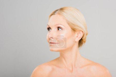 Photo pour Attrayant et blonde mature femme regardant loin sur fond gris - image libre de droit
