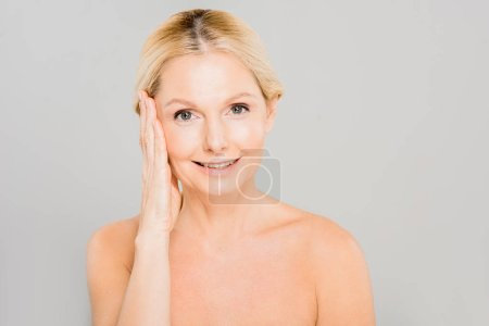 attractive and smiling mature woman touching her face and looking at camera isolated on grey