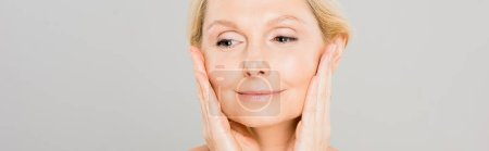 Photo for Panoramic shot of attractive and smiling mature woman touching her face and looking away on grey background - Royalty Free Image