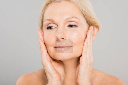 Photo pour Attrayant et blonde femme mature toucher son visage et détourner les yeux sur fond gris - image libre de droit