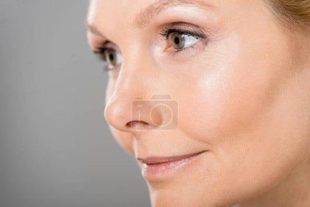 Photo pour Foyer sélectif de la femme attrayante et mature regardant loin isolé sur gris - image libre de droit