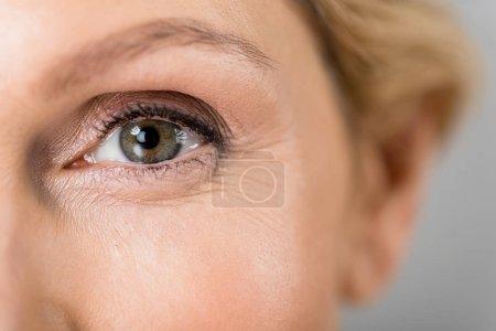 Photo pour Foyer sélectif de la femme mature regardant la caméra isolée sur gris - image libre de droit