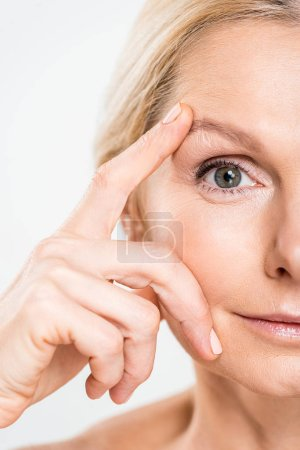 Photo for Partial view of mature woman looking at camera and touching her face isolated on grey - Royalty Free Image