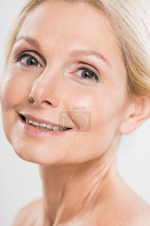 Photo for Beautiful and happy mature woman looking at camera on grey background - Royalty Free Image