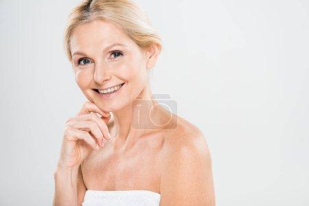 Photo pour Femme mûre séduisante et souriante regardant la caméra et de toucher son visage sur fond gris - image libre de droit