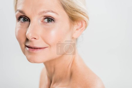 Photo for Attractive and blonde mature woman looking at camera isolated on grey - Royalty Free Image