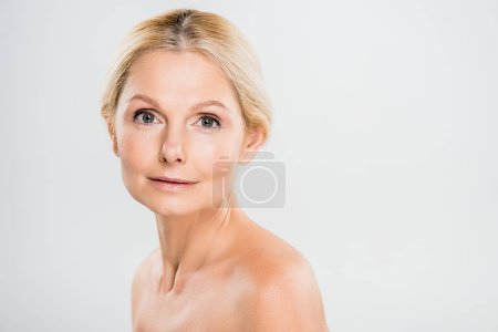 beautiful and blonde mature woman looking at camera on grey background