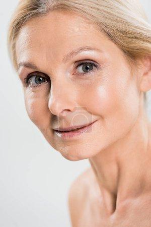 Photo pour Gros plan de belle femme mature blonde regardant caméra isolée sur fond gris - image libre de droit