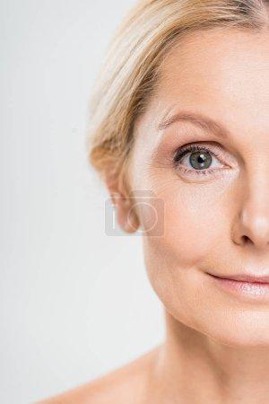 Photo pour Vue partielle de femme mature regardant la caméra isolée sur gris - image libre de droit
