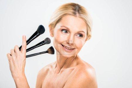 Photo pour Femme mure belle et souriante cherche loin et holding cosmétiques brosses sur fond gris - image libre de droit