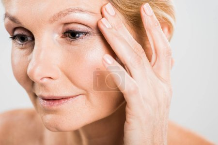 Photo for Beautiful mature woman touching her face and looking away isolated on grey - Royalty Free Image