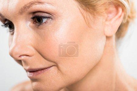 Photo pour Foyer sélectif de belle femme mature regardant loin isolé sur gris - image libre de droit