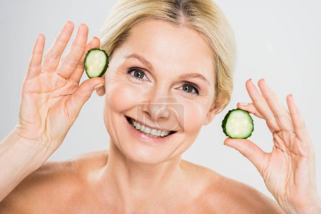 Photo for Beautiful and smiling mature woman holding cut cucumber and looking at camera on grey background - Royalty Free Image
