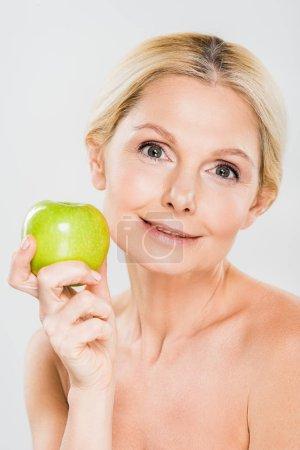 Photo pour Belle femme d'âge mûr tenant pomme verte et en regardant la caméra sur fond gris - image libre de droit
