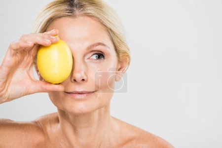 Photo for Beautiful and mature woman holding ripe lemon and looking away isolated on grey - Royalty Free Image