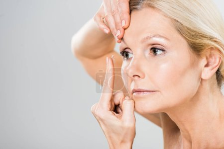 selective focus of beautiful woman attaching contact lens isolated on grey