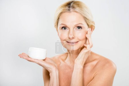 beautiful and happy mature woman looking at camera and applying cosmetic cream