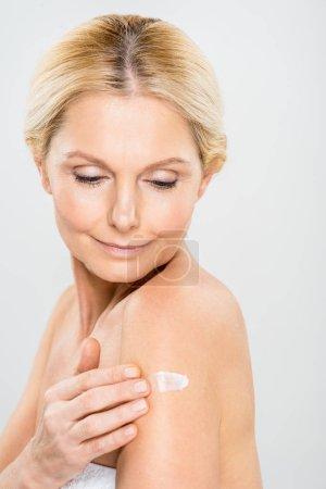 Photo pour Belle et mature femme regardant vers le bas et l'application de crème cosmétique sur l'épaule isolé sur gris - image libre de droit