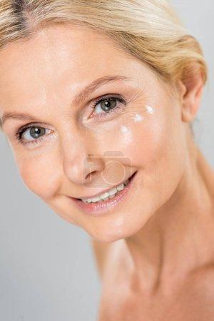 Photo pour Portrait d'une femme belle et mature, regardant la caméra avec crème cosmétique visage isolé sur fond gris - image libre de droit