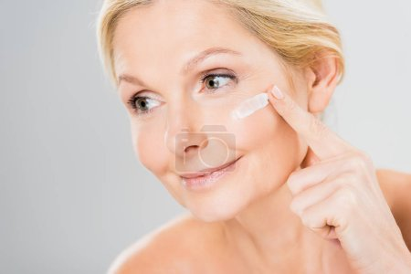 Photo for Beautiful and mature woman looking away and applying cosmetic cream on face - Royalty Free Image