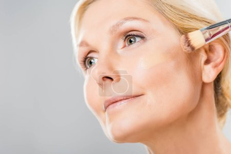 Photo for Beautiful and mature woman looking away and applying makeup foundation with cosmetic brush isolated on grey - Royalty Free Image