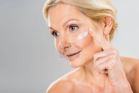 Foto de Mujer hermosa y madura mirando lejos y aplicar crema cosmética en la cara - Imagen libre de derechos