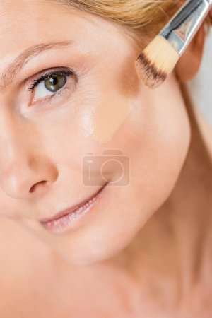 Photo pour Selective focus of beautiful and mature woman looking at camera and applying makeup foundation with cosmetic brush - image libre de droit