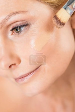 Photo pour Selective focus of beautiful and mature woman looking away and applying makeup foundation with cosmetic brush - image libre de droit