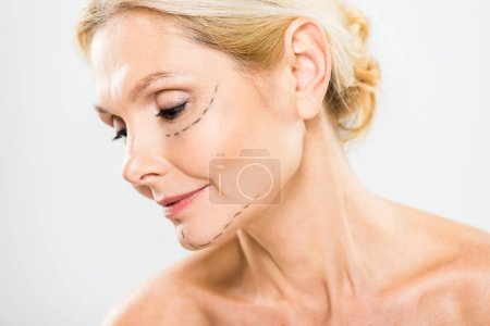 Photo for Beautiful and middle aged woman with lines on face looking down on grey background - Royalty Free Image