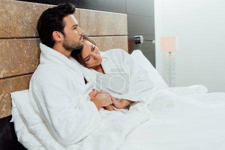 Photo pour Bel homme hugging superbe copine en position couchée dans son lit - image libre de droit