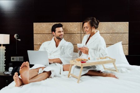 cheerful man using laptop and looking at beautiful girlfriend with cup of coffee