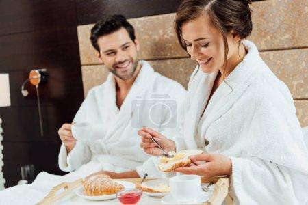 Foto de Hombre alegre en hermosa mujer sosteniendo el croissant y la cuchara en la cama - Imagen libre de derechos
