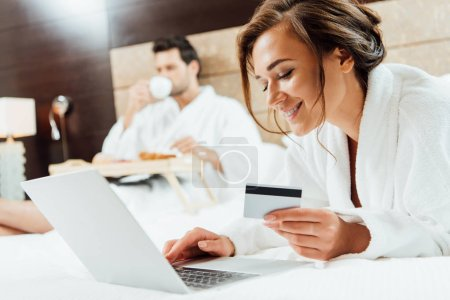 selective focus of happy woman using laptop while holding credit card near boyfriend