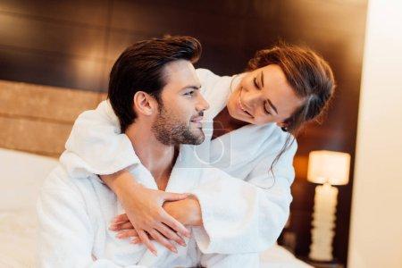 Photo for Happy girlfriend in white bathrobe embracing handsome boyfriend - Royalty Free Image