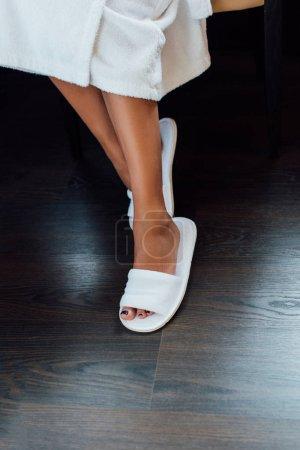 Photo pour Recadrée vue de pieds féminins en pantoufles blanches hôtel - image libre de droit