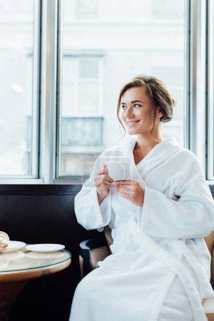 Photo pour Jolie femme brune en peignoir assis et tenant une tasse de café - image libre de droit