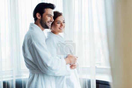 Photo pour Foyer sélectif de l'homme joyeux étreignant femme heureuse en peignoir blanc à l'hôtel - image libre de droit