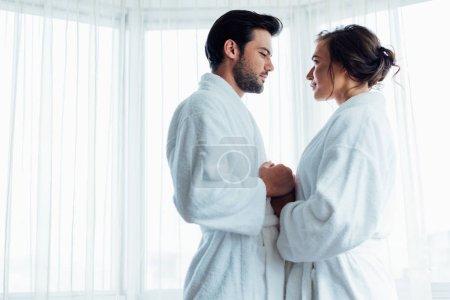Photo pour Bel homme barbu tenant la main avec une femme heureuse en peignoir blanc à l'hôtel - image libre de droit