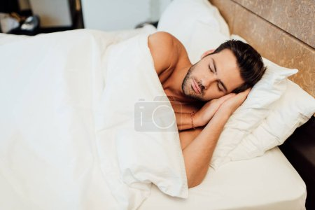 Photo for Handsome bearded man sleeping under blanket in bed - Royalty Free Image