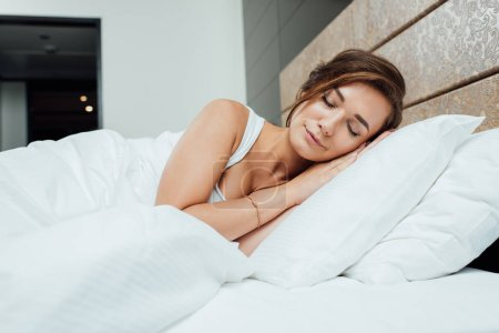 attractive brunette woman sleeping on pillows under blanket in bed