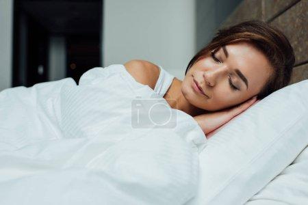 beautiful brunette woman sleeping on pillow under blanket in bed