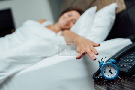 Photo for Selective focus of retro blue alarm clock near woman in bed - Royalty Free Image